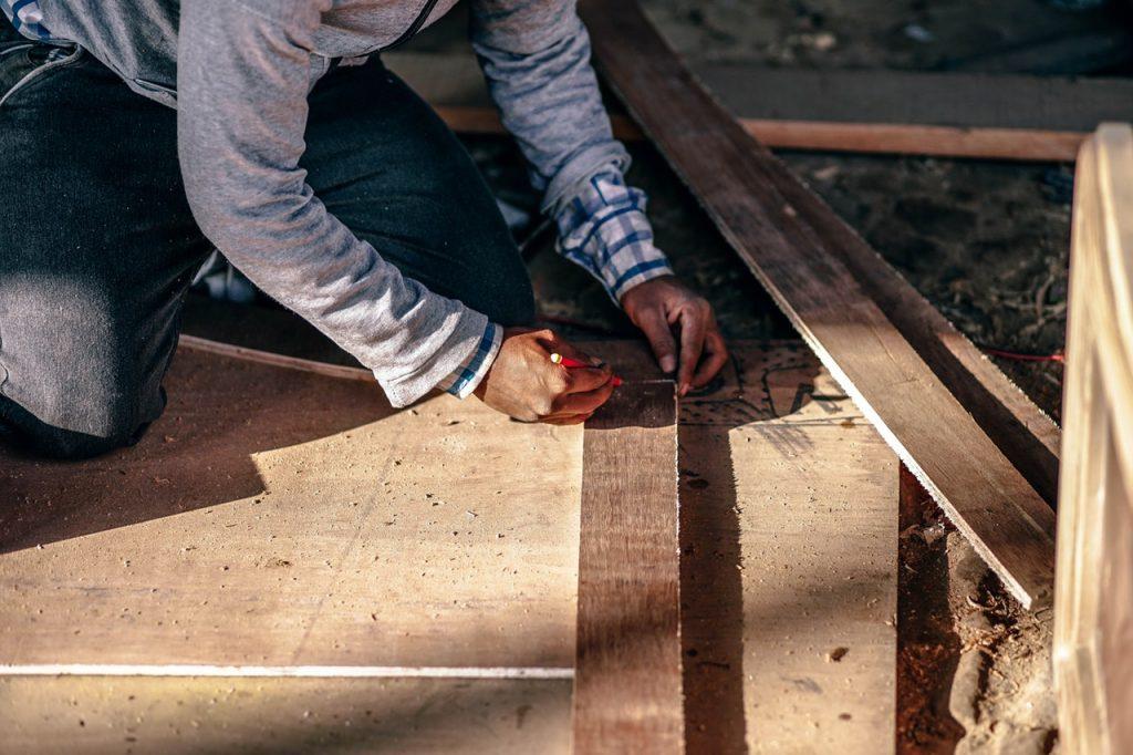 Worker Measuring Size Wood For Renovation